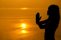Woman with namaste hands at sunset